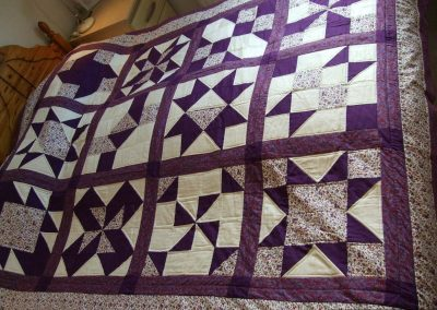 A quilt using purple and cream with various blocks